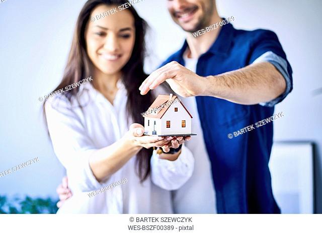 Couple holding new house model