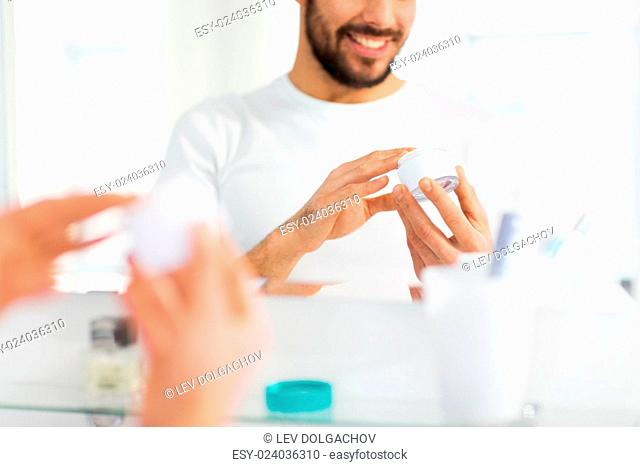 beauty, skin care and people concept - close up of happy young man with facial cream at bathroom