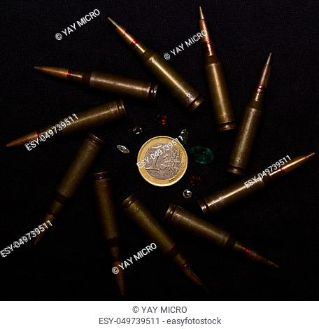 Rifle ammo with a lot of gemstones around one euro coin on black background. Symbolizes the war for money and one of the world's problems