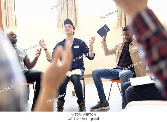 Men with bible praying with arms raised in prayer group
