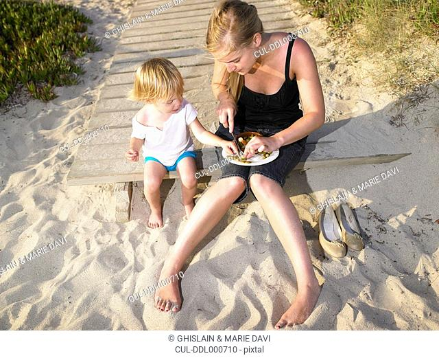 Woman sitting with a young boy eating at the beach