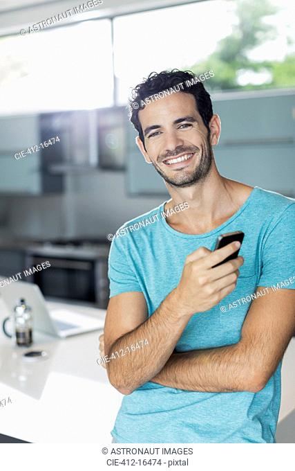 Portrait of smiling man with cell phone in kitchen