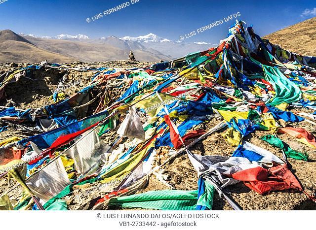 Tibetan prayer flags at the summit of Kamba-la (4794m) with Mt Nojin Kangtsang (7191m) Tsang, Tibet