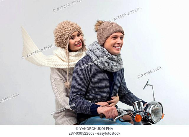 I love traveling with you. Pretty loving couple is riding the scooter with joy in winter. They are sitting and laughing. Isolated