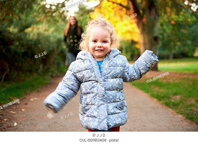 Happy female toddler running in autumn park