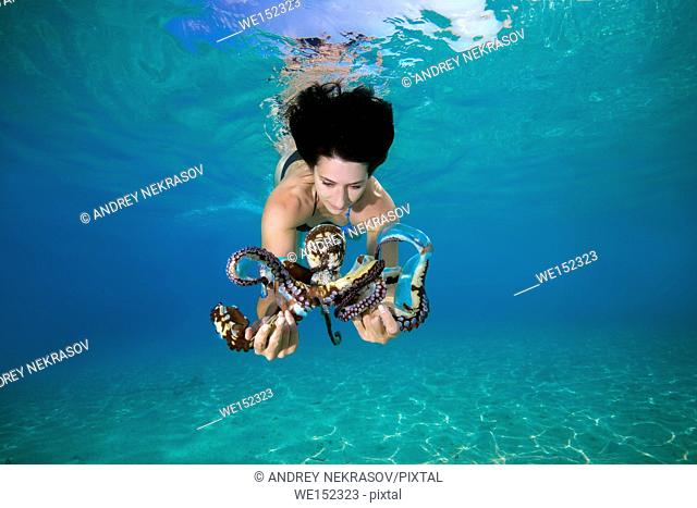 beautiful black-haired woman in dress with Big Blue Octopus (Octopus cyanea) in Indian Ocean, Maldives