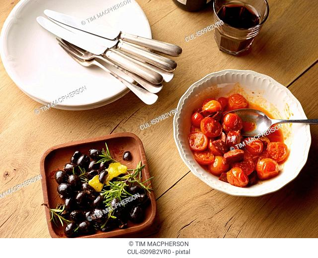 Overhead view of table with bowl of black olives and bowl of Spanish tomatoes with chorizo