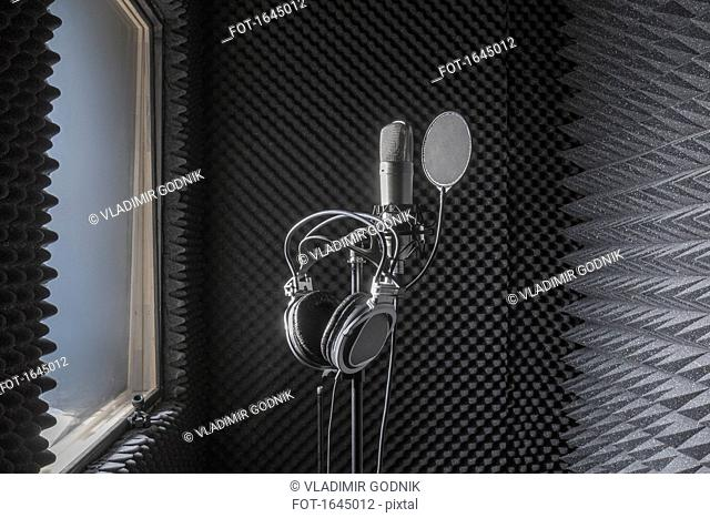 Close-up of headphones on microphone stand in soundproof recording studio
