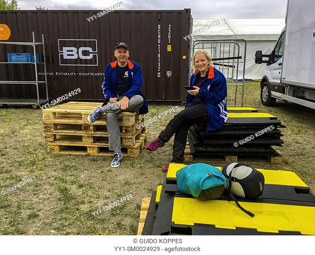 Hamburg, Germany. Two co-workers taking a break aet the Roparun 2018 Compound inside the Reiherstiegknie Park, the day before Event Launch