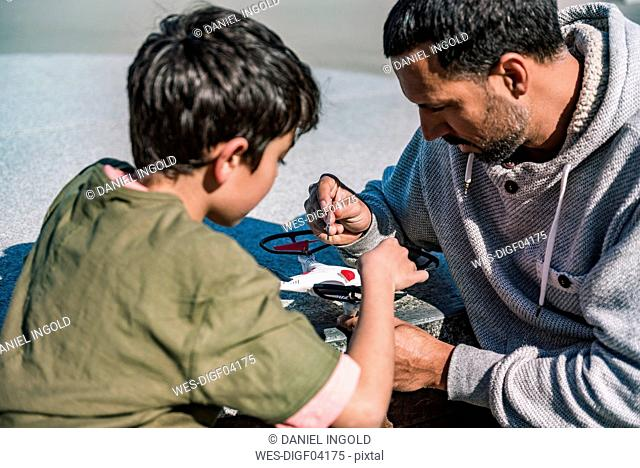 Father and son repairing drone