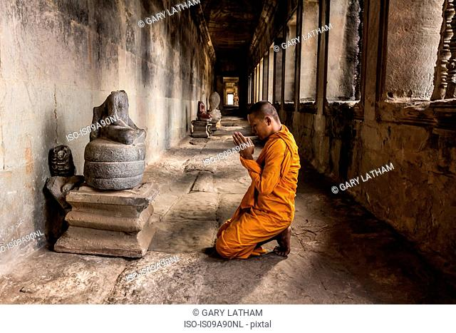 Young Buddhist monk praying in temple, Angkor Wat, Siem Reap, Cambodia