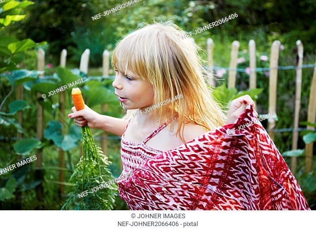 Girl eating carrot in field