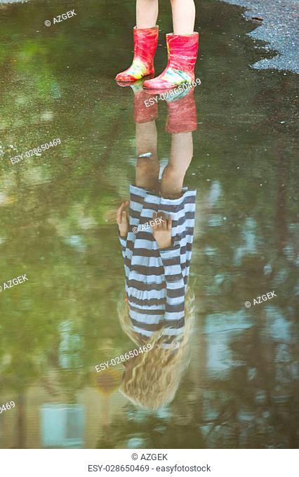 girl in gumboots is reflected in a puddlel, summer