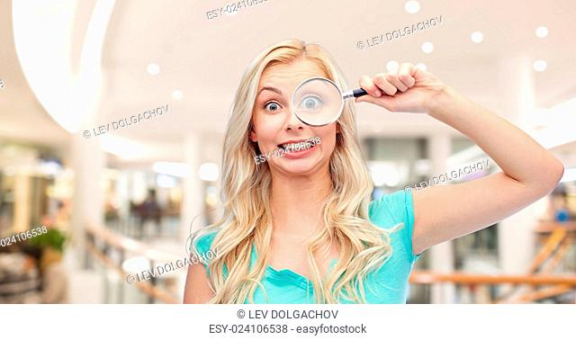 vision, exploration, investigation, education and people concept - happy smiling young woman or teenage girl looking through magnifying glass over mall or...
