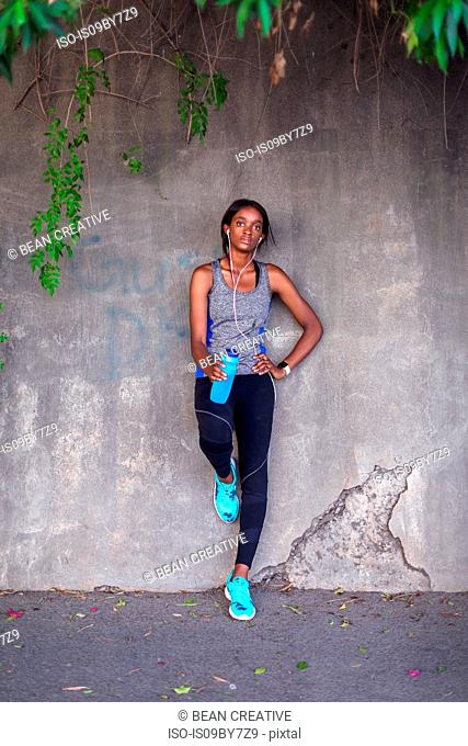 Young female runner listening to earphones leaning against city sidewalk wall, portrait