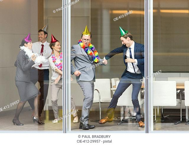 Playful business people in party hats dancing at conference room window