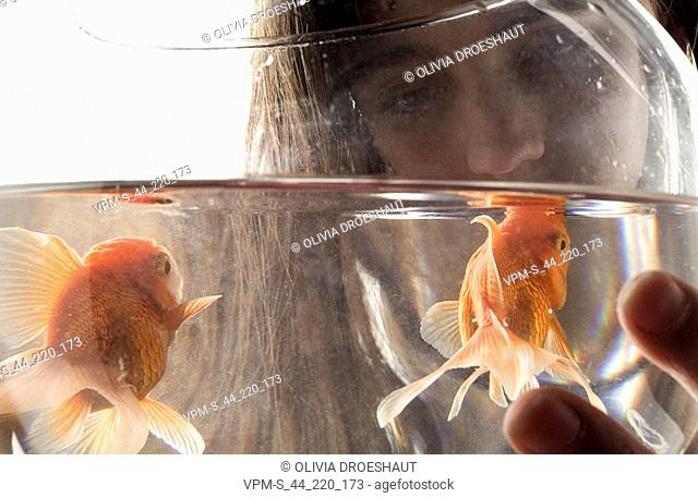 Close-up of a young woman holding a goldfish bowl