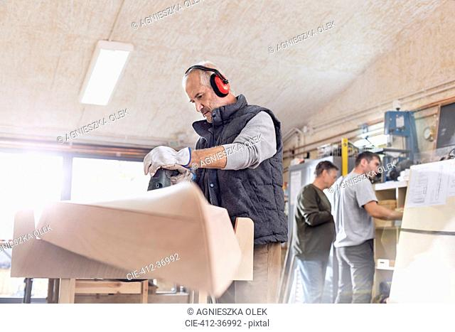 Senior carpenter using sander, sanding wood boat in workshop