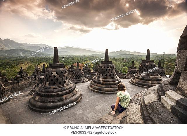 Tourist in unroofed pyramid of Borobudur Temple, crowned by bell-shaped stone domes (Magelang Regency, Central Java, Indonesia)