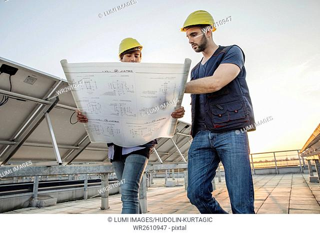 Architect and engineer inspecting solar power station