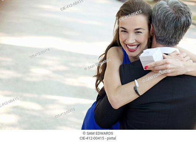 Portrait of smiling woman receiving gift from man