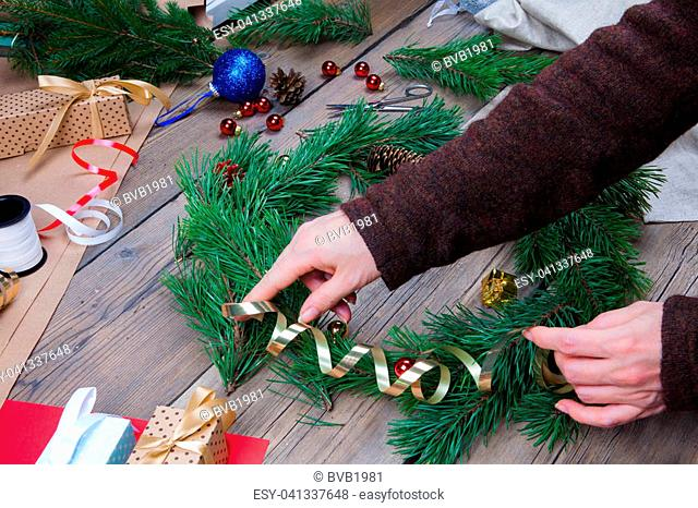 Woman is making Christmas wreath. Handmade gift
