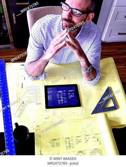 High angle view of an architect working on a technical drawing, using a digital tablet