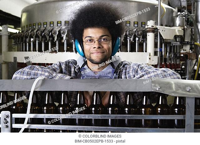 Man behind conveyor belt wearing earphones