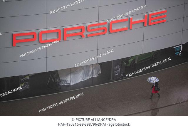 15 March 2019, Baden-Wuerttemberg, Stuttgart: A woman with an umbrella passes the Porsche headquarters in Stuttgart before the Porsche AG balance sheet press...