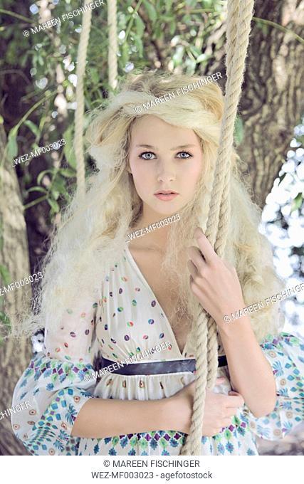 Blond teenage girl at swing rope