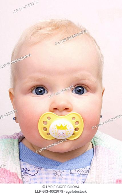 Suckling baby, 7 months, with yellow dummy