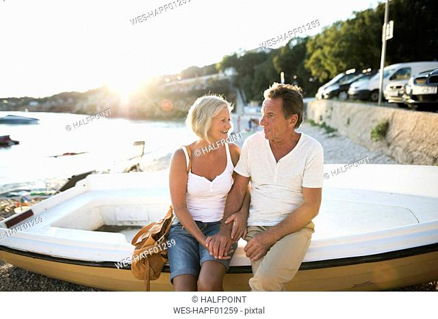 Senior couple sitting on edge of a boat on the beach at evening twilight
