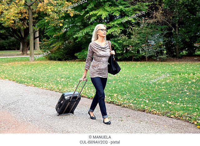 Mature woman walking through park pulling wheeled suitcase