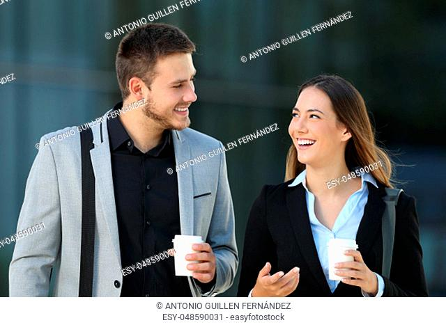 Happy couple of executives walking towards camera and conversing on the street with an office building in the background