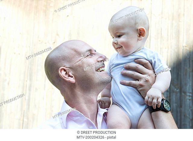 Father holding baby son proud smiling happy
