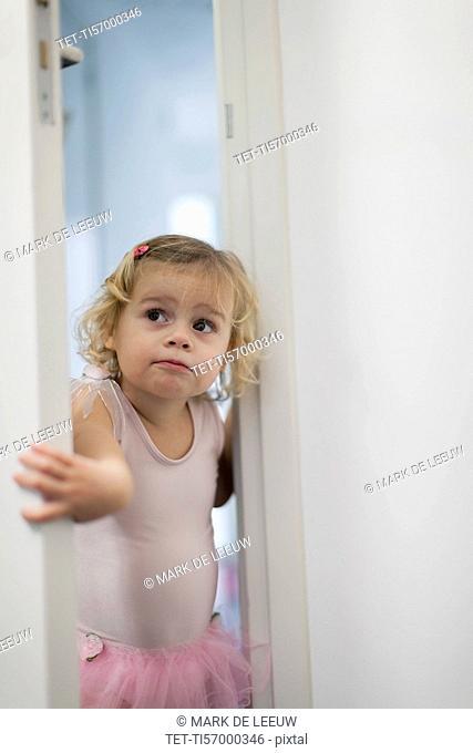 Girl (2-3) in pink skirt opening bedroom door