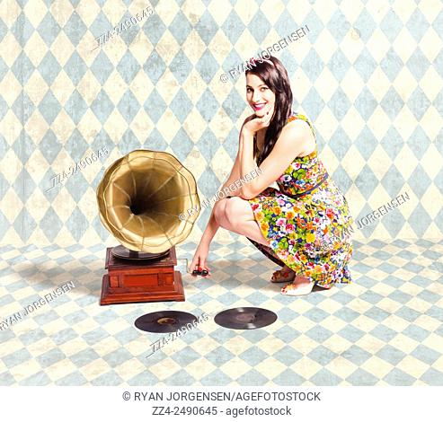 Old audio picture of a pretty pin up girl listening to classical music on old phonograph in tiled grunge room. Gramophone girl