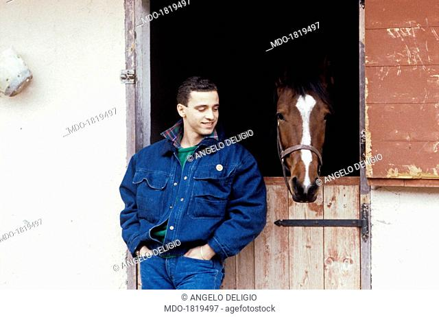Italian singer-songwriter Eros Ramazzotti smiling looking at a horse. Italy, 1986