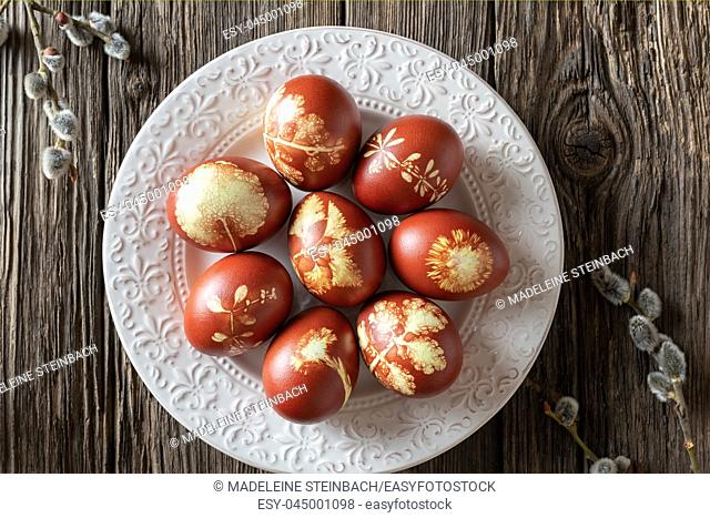 Easter eggs dyed with onion peels with a pattern of fresh herbs on a vintage plate