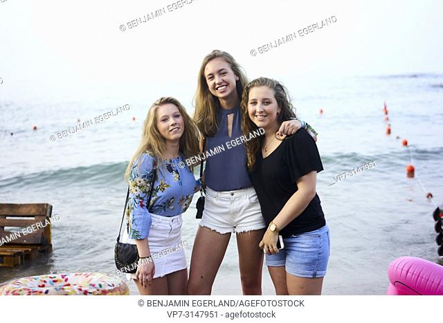 Greece, Crete, Hersonissos, three friends posing on the beach, together at Beachparty