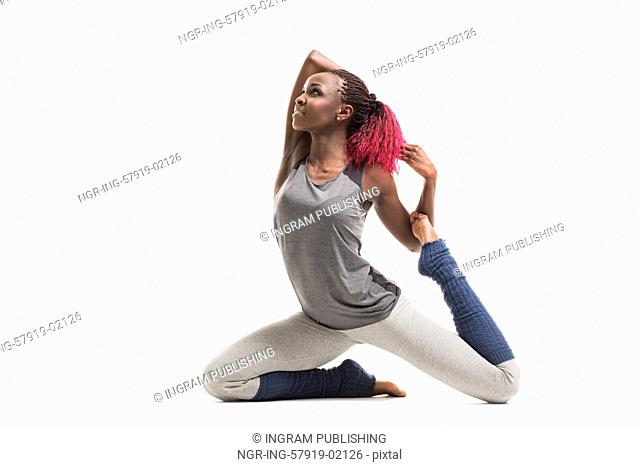 Young african woman doing yoga exercises isolated on white background