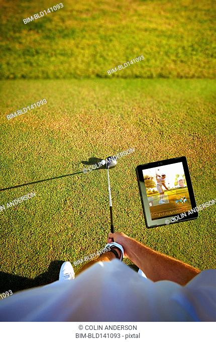 High angle view of Caucasian golfer holding club at ball near digital tablet
