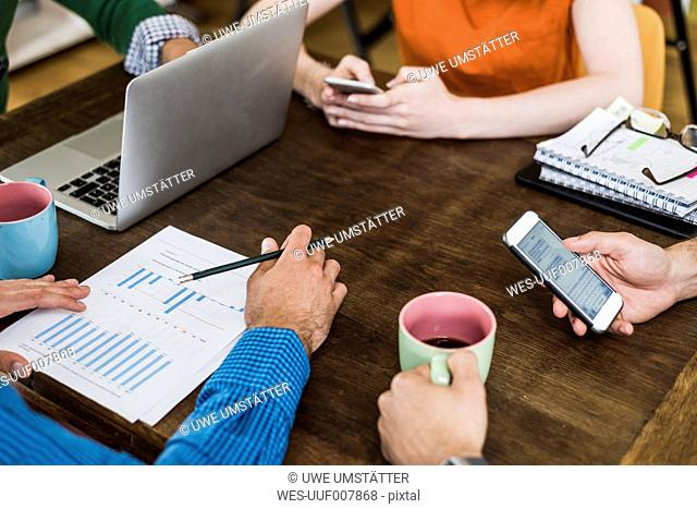 Colleagues at table with cell phones, laptop and document
