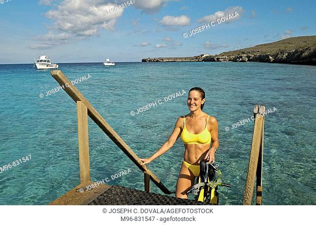 Female snorkeler coming out of ocean, Curaçao, Netherland Antilles, Caribbean