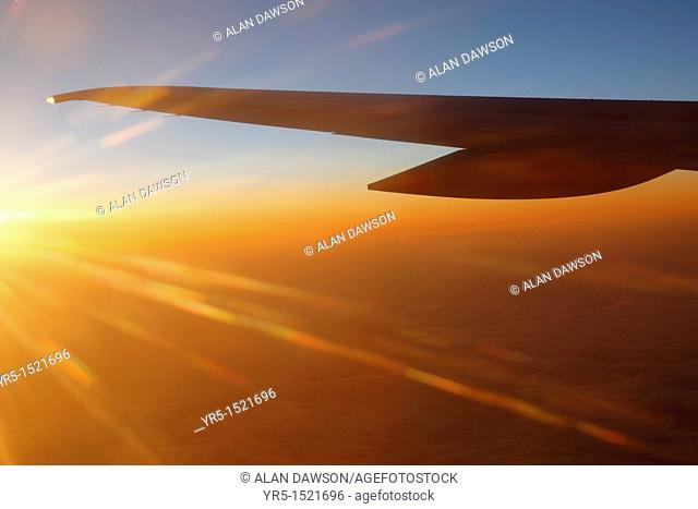 View of airplane wing over layer of cloud at sunset