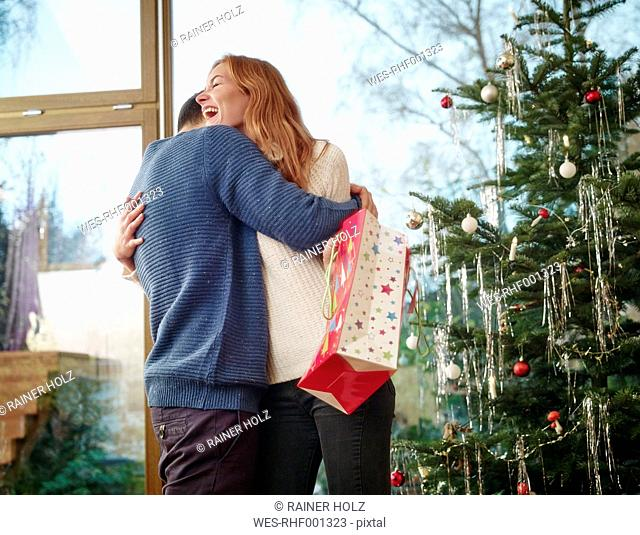 Couple standing in front of Christmas tree