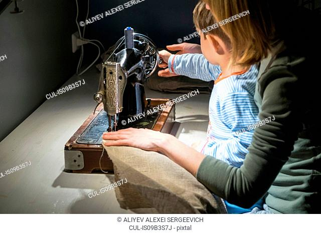 Over shoulder view of boy with mother learning to turn sewing machine handle