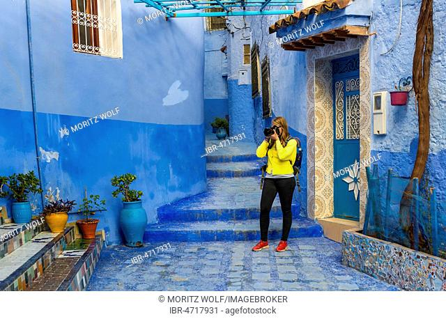 Young woman photographed, Blue house walls, Medina of Chefchaouen, Chaouen, Tangier-Tétouan, Kingdom of Morocco