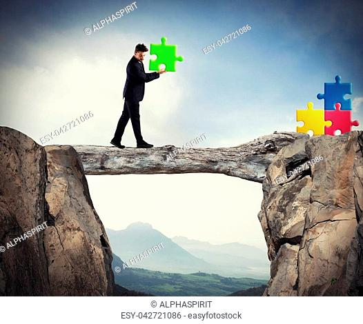 Businessman carries a piece of puzzle while he walking on a tree trunk between the mountains. concept of missing piece