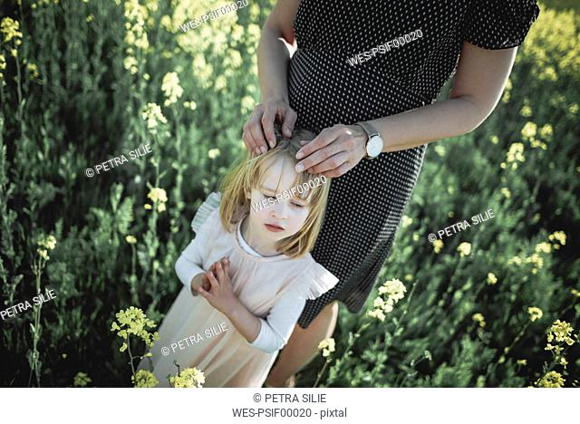 Portrait of little girl standing with her mother in rape field